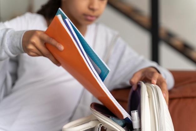 学校のために彼女のバックパックを準備している女の子