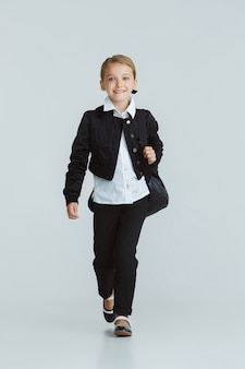 Girl preparing for school after a long summer break. back to school. little female caucasian model posing in school's uniform on white  wall. childhood, education, holidays concept.