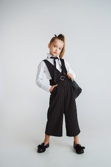 Girl preparing for school after a long summer break. back to school. little female caucasian model posing in school's uniform with backpack on white background. childhood, education, holidays concept.