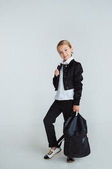 Girl preparing for school after a long summer break. back to school. little female caucasian model posing in school's uniform with backpack on white wall. childhood, education, holidays concept.