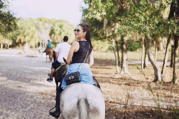 Девушка готовится кататься на лошади