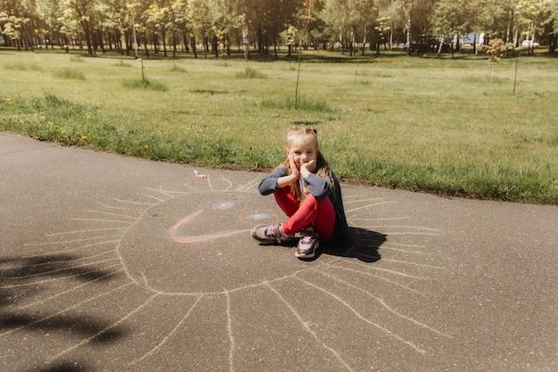 여자 미취학 아동은 공원에서 여름에 아스팔트에 분필로 그립니다.