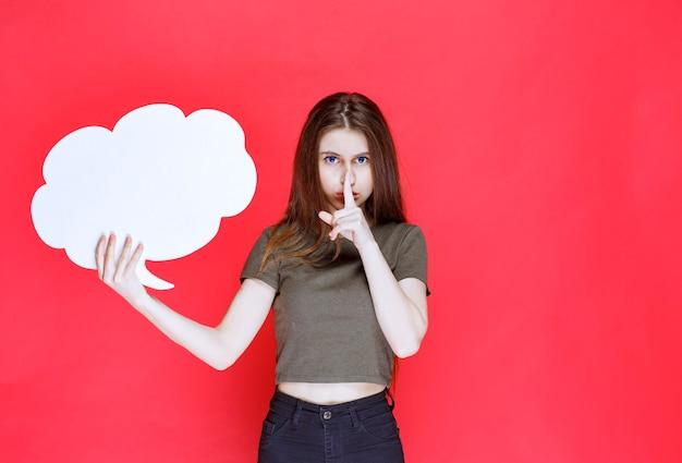 雲の形の情報ボードを提示し、沈黙を求める少女。