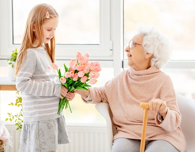 Girl presenting bouquet to old woman
