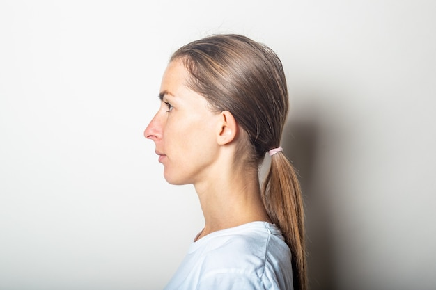 Girl in profile with protruding ears, on a light wall