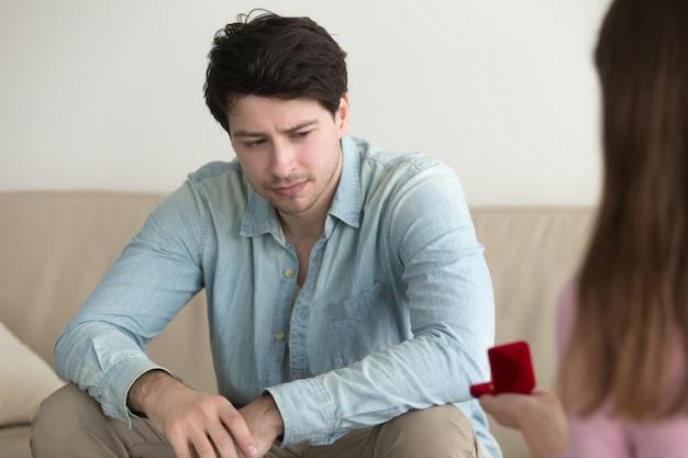Девушка делает предложение мужчине, смущенный парень смотрит нахмурившись и озадаченный