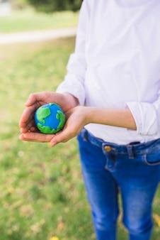 Ragazza che protegge il globo di argilla con le sue mani