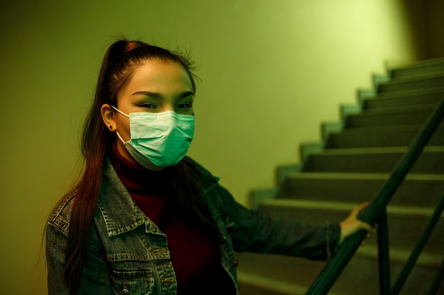 Girl in a protective disposable medical mask at stairwell