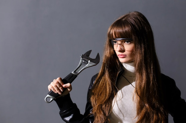 Girl in protective glasses with adjustable wrench on a dark background