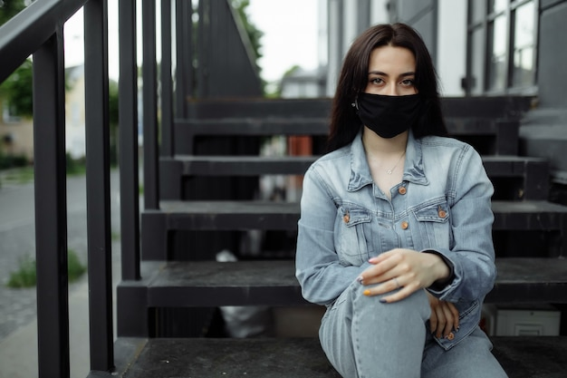 Girl in a protective mask on a balcony looks at an empty city.