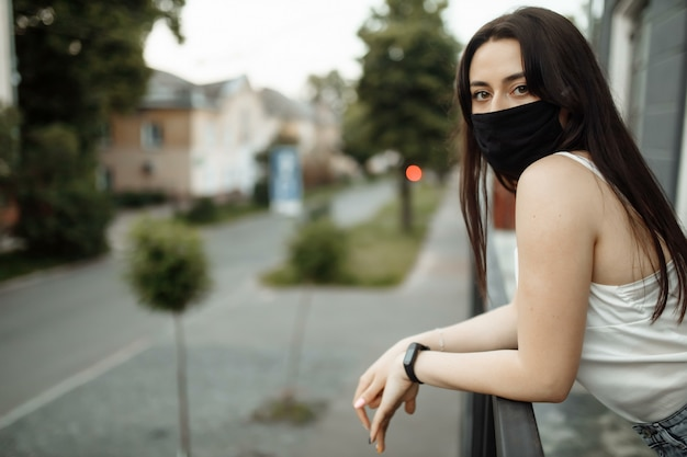 Girl in a protective mask on a balcony looks at an empty city