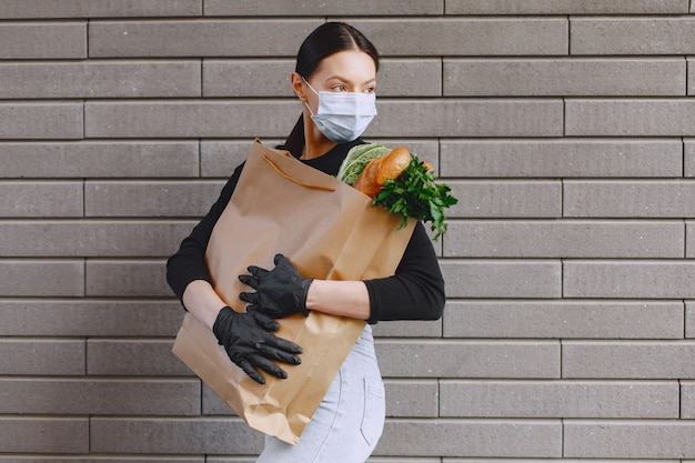 Girl in protective mask holds package with products