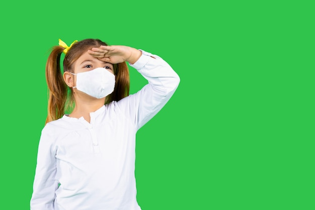 A girl in a protective medical mask looks into the distance on a green isolated background holding her hand