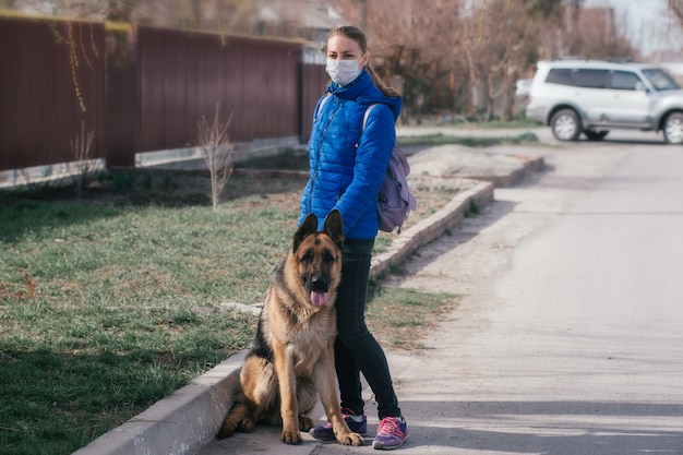 A girl in a protective medical mask walks a dog on the street. leisure with a pet during quarantine. self-isolation and protection mode.