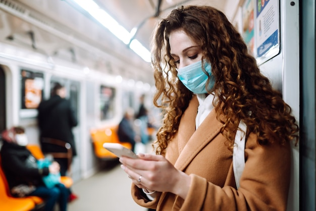 Girl in protective sterile medical mask on her face with a phone in a subway car. woman using the phone to search for news about coronavirus. the concept of preventing the spread of the epidemic.