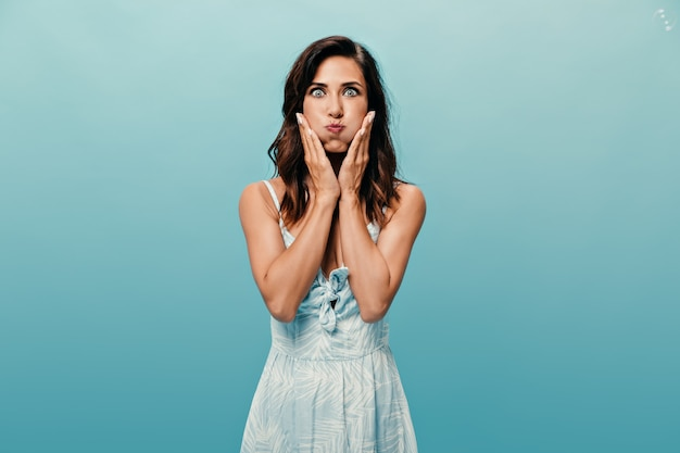 Girl puffed out her cheeks and looks into camera on blue background. adorable woman in light outfit with short hair having fun on blue background.