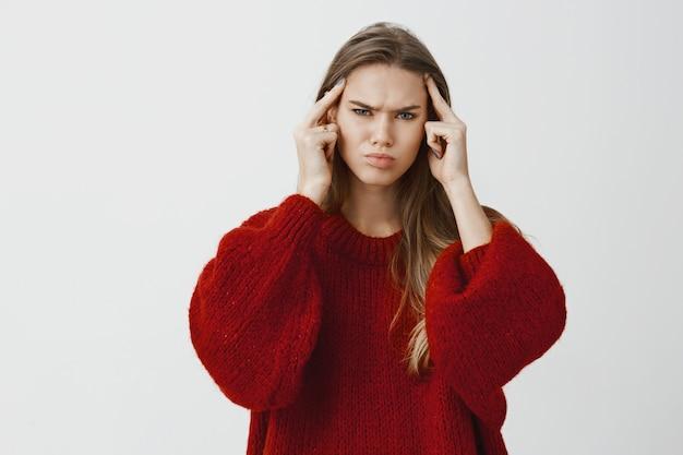 Девушка тянет все усилия, чтобы найти решение или вспомнить что-то. портрет сфокусированной обеспокоенной молодой женщины, держащей указательные пальцы в храмах и хмурящейся, пытающейся сосредоточиться на проблеме над серой стеной