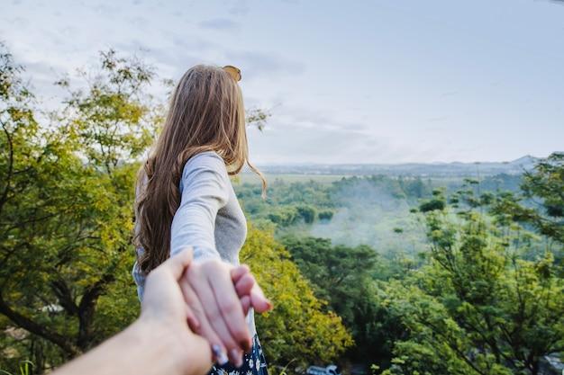 Girl pulling boyfriends hand in countryside