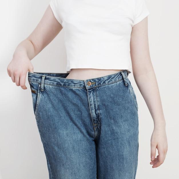 Девушка тянет свои большие джинсы и показывает потерю веса