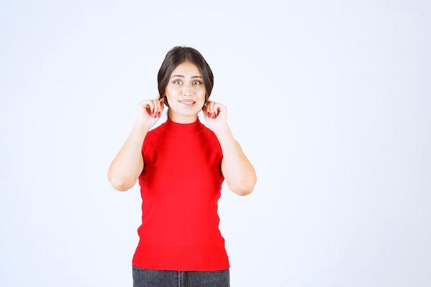 Девушка дергает за уши в знак невезения.