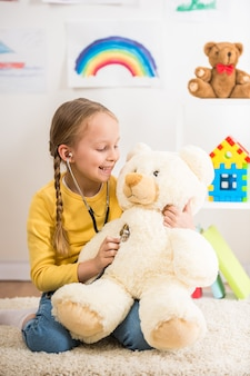 Girl in pullover playing with bear