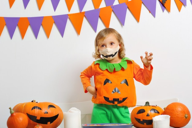 Girl in the pumpkin costume are celebrating halloween wearing face masks protecting from covid19