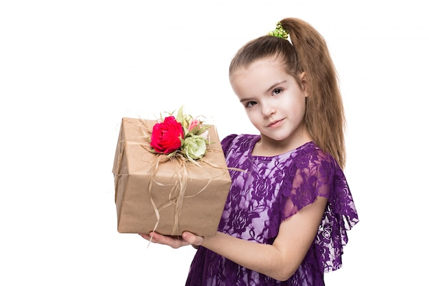 Girl in purple lace dress holding a box with a gift decorated with flowers.