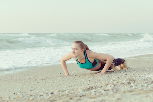 Girl push-ups on the beach, waves
