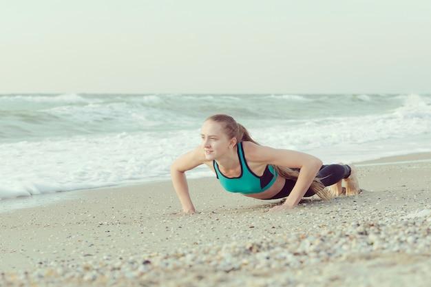 Девушка отжимания на пляже, волны