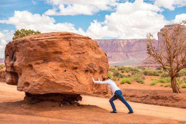 Девушка толкает большой камень трудно, невозможно и бесполезно