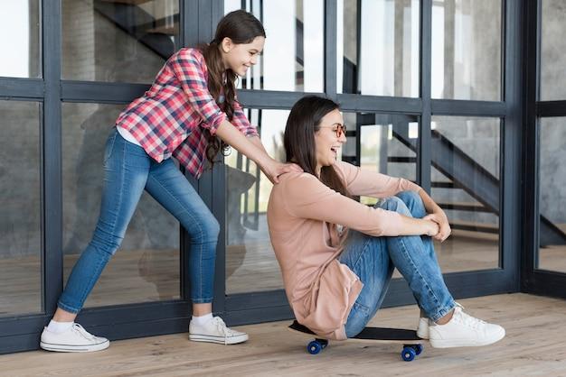 スケートボードでママを押す女の子
