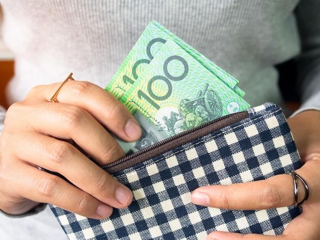 여자는 주머니에 달러 호주 돈을 넣어.