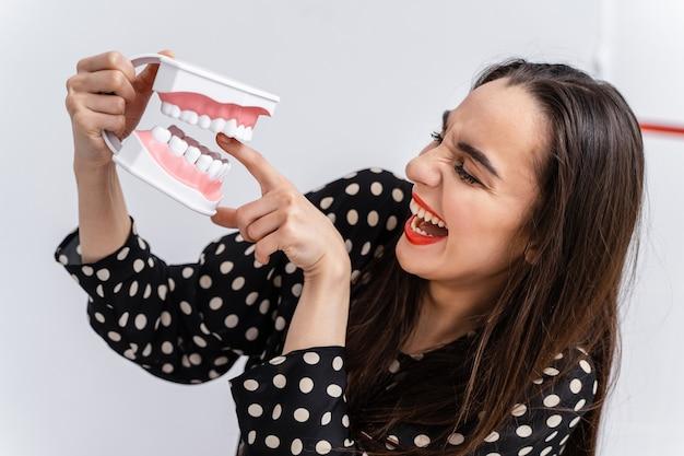 女の子は歯科教育の顎に指を置きました。プラスチック製のあごが女の子を指で噛みます。面白い感情。