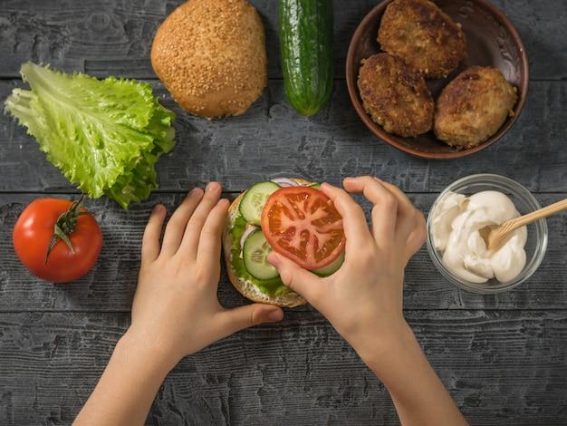 여자는 햄버거에 토마토 한 조각을 넣습니다.