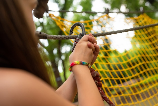 Girl puts a carabiner on a rope in a rope park
