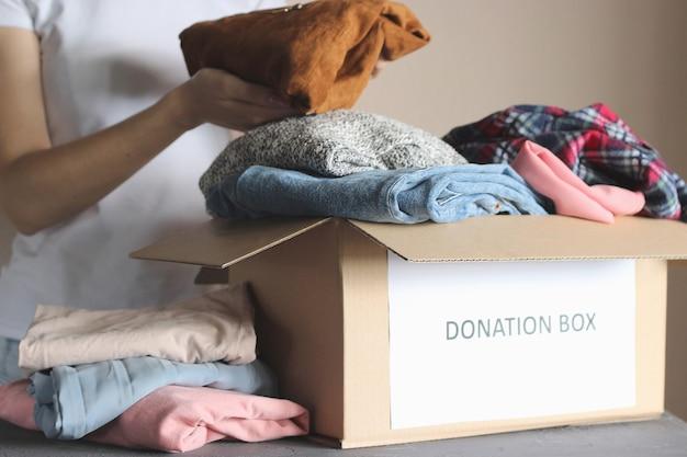 소녀는 자원 봉사 기부 품목이 있는 상자에 넣습니다.