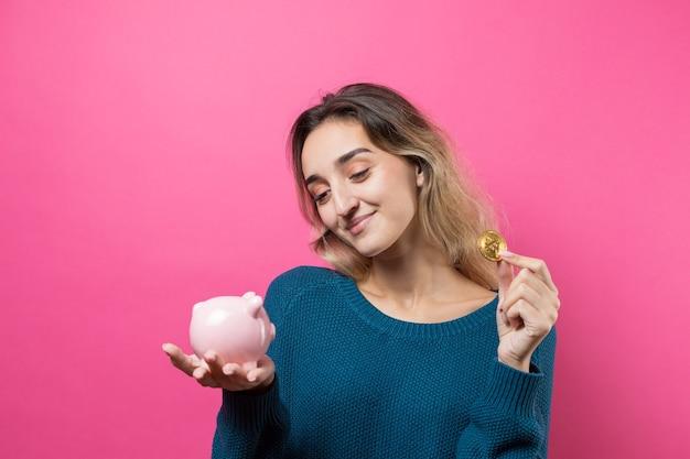 소녀는 돼지 저금통에 물리적 bitcoin을 넣습니다. 돼지 저금통을 들고 분홍색 배경 위에 어린 소녀
