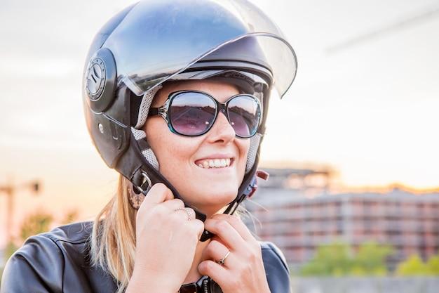 Девушка надевает шлем, чтобы поехать на скутере