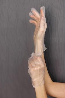 Девушка надевает медицинские перчатки на сером фоне