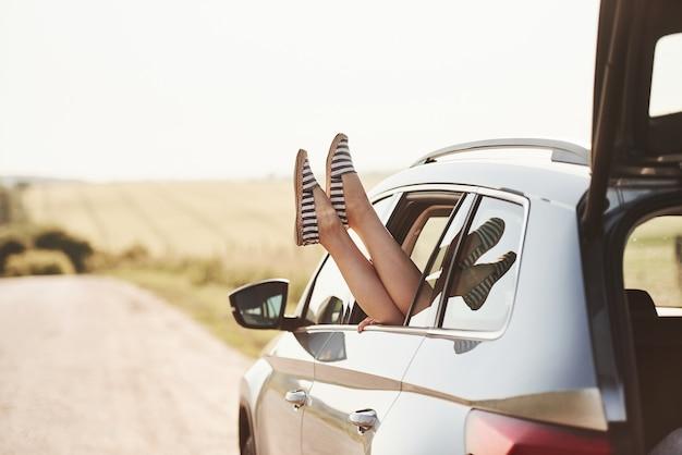 女の子は田舎の自動車の窓に足を出します