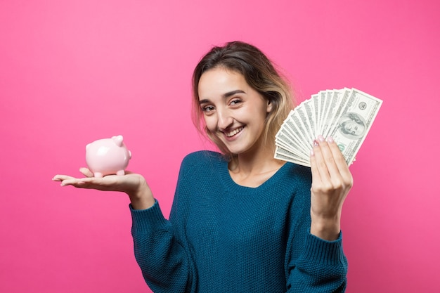 Girl puts in the piggy bank one hundred dollar bills young girl holding piggy bank