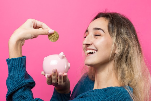 Girl puts in the piggy bank physical bitcoinyoung girl over pink background holding piggy bank