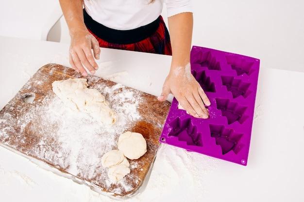 소녀는 생 반죽을 케이크 형태로 넣습니다.