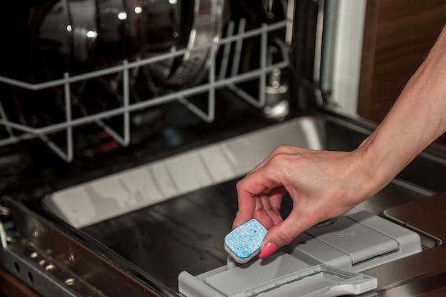女の子は食器洗い機用洗剤の入った箱にタブレットを入れます。