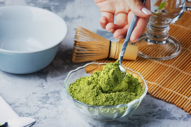 Girl puts a teaspoon of green tea powder in a bowl. matcha green tea powder, whisk and bowl.