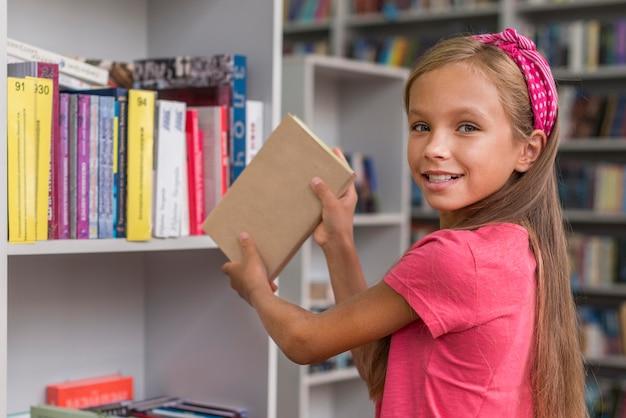 Девушка кладет книгу на полку