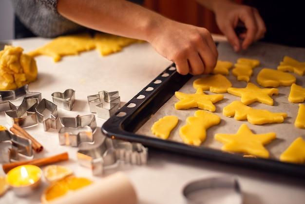 天板にクリスマスクッキーを置く女の子