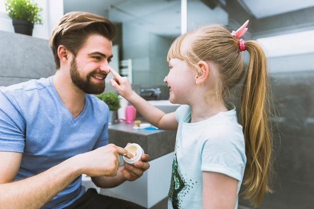 父親の鼻にクリームを塗った少女