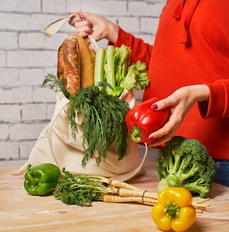Girl putting greens and fresh leek on the kitchen table out of the cotton reusable tote bag, using eco shopper instead of a plastic bag, concept of healthy lifestyle