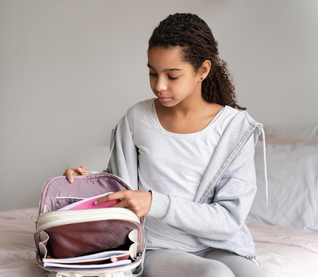 Girl putting her books in the backpack